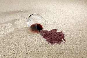 a wine glass spilled on a carpet that needs stain removal services