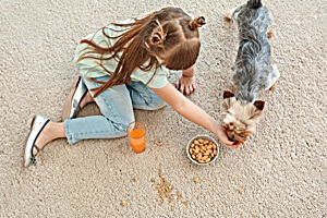 Girl and dog on stained carpet