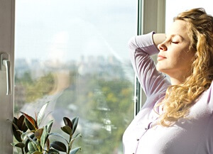 Woman standing near window and plant clean air