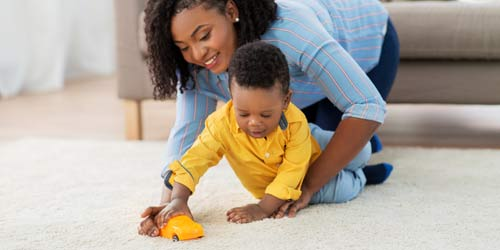 mother playing with son on safedry cleaned carpet