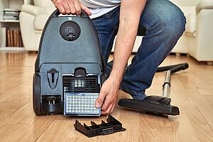 Man replacing HEPA high efficiency particulate air filter on vacuum