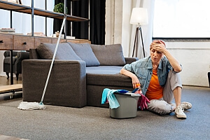 Woman sitting on carpet frustrated at cleaning
