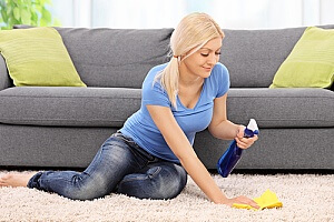 a woman removing mold from her carpet using a bleach solution