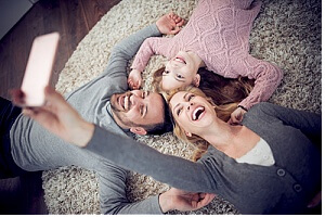 family taking group selfie on carpet after a professional carpet cleaning