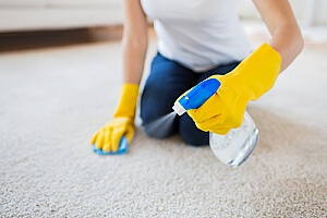 a woman cleaning her carpet that had a stain